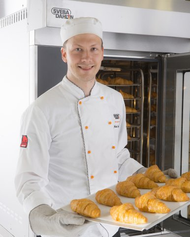 Baker baking croissants using Sveba Dahlen S-series Mini Rack Bakers Oven